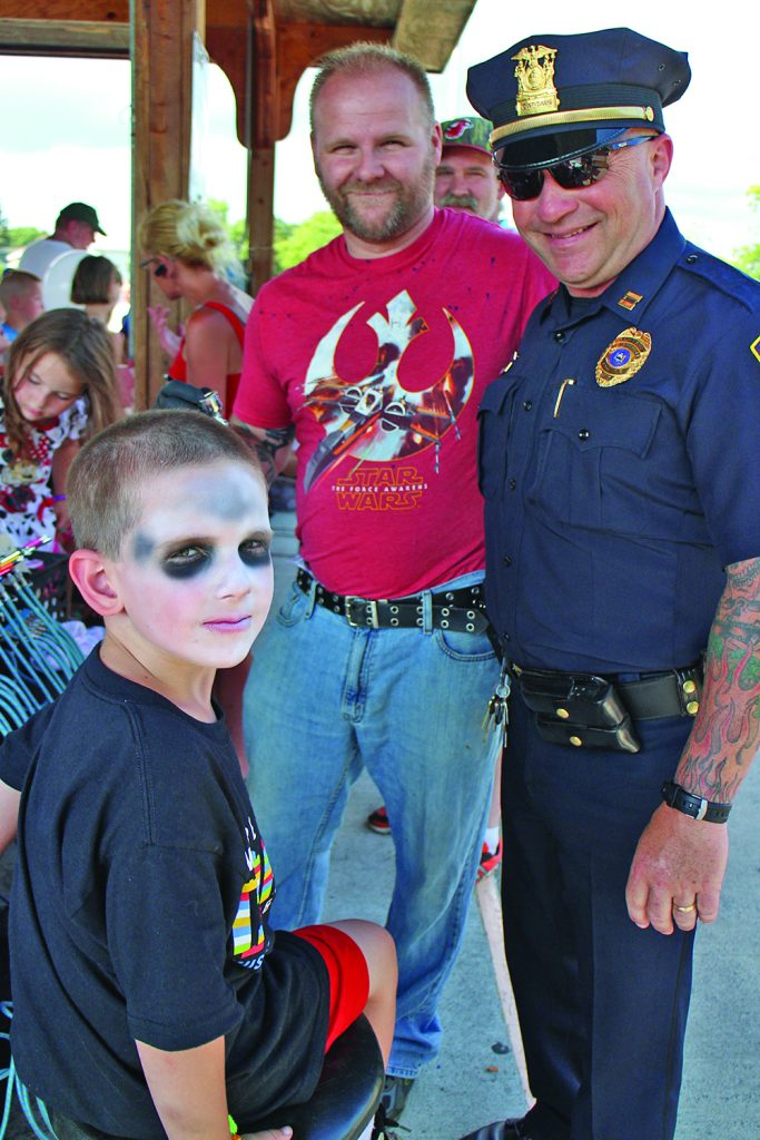 Gloversville Police Department Capt. Mike Scott, right, stands with Caleb Devanney, left, who just had his face painted by Henry Araujo, center, of Extreme Ink in Gloversville.