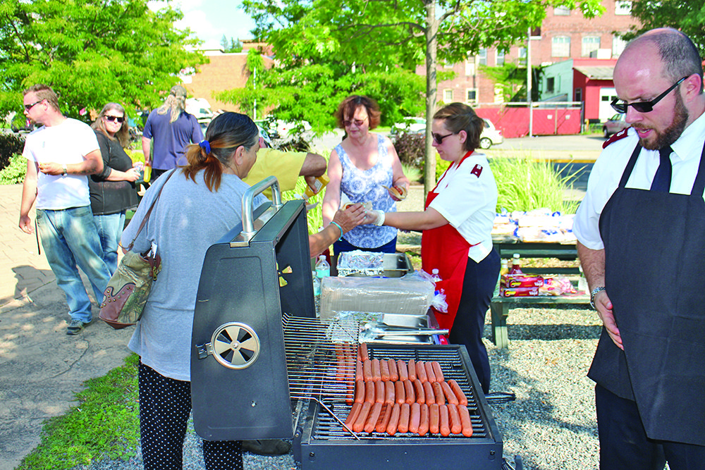 Lt. Mark Devanney and Lt. Ann Marie Devanney volunteer with the Salvation Army to provide attendees with hotdogs.