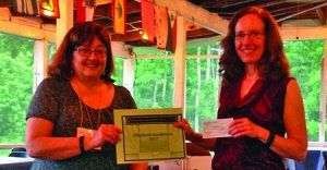Photo submitted AAUW Co-President Catherine Julius presents FMCC graduate, Elizabeth Gundersen with a $1000 scholarship check to continue her studies in the pursuit of a bachelor's degree.