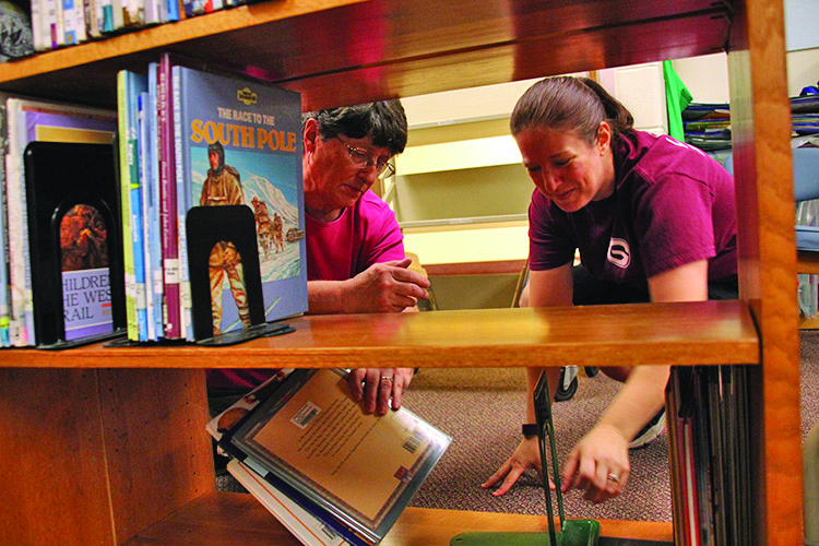 Photo submitted Michelle Armstrong, right, and Bonnie Schwartz shelve books in the library at Boulevard Elementary. They have been restructuring the library to accommodate for thousands of new books, many of which came from the former McNab Elementary.
